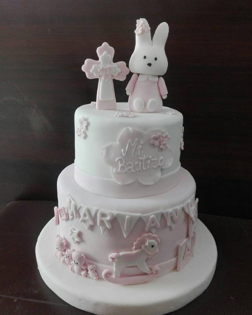 ponque mi bautizo con conejo y osos en colores blanco y rosa.