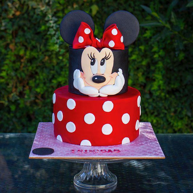 Ponque 2 pisos rojo y pepas blancas, rostro de Minnie Mouse y orejas.