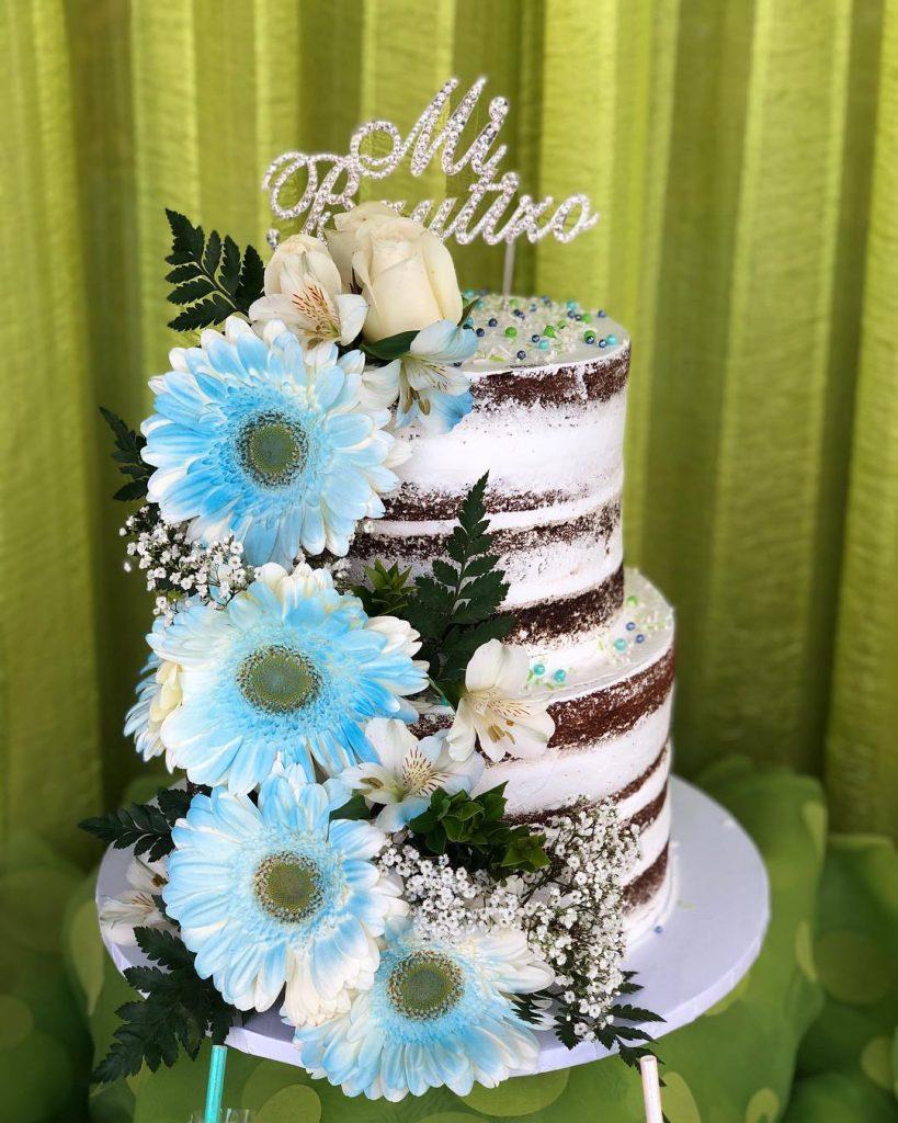 Ponque estilo rústico de 3 pisos decorado con flores azules y topper en color plata.
