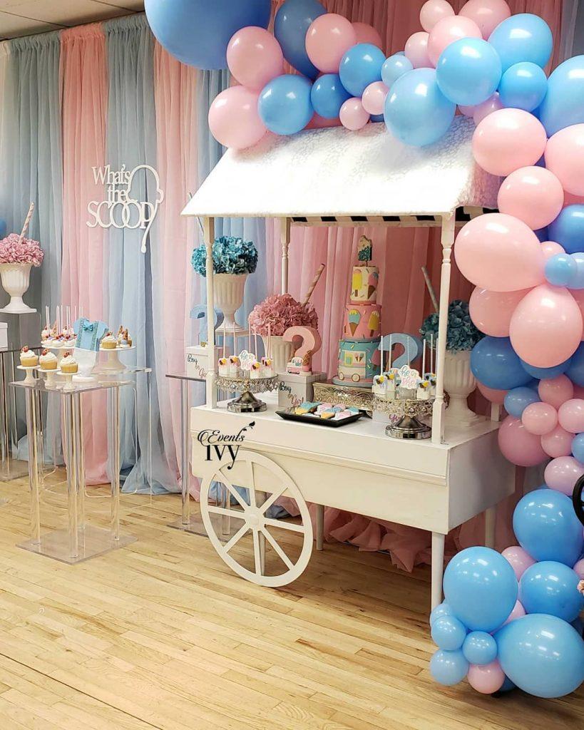 Carrito para mesa dulce rosa y azul con globos.
